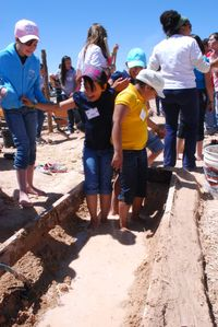 Students mix mud for earthen garden beds